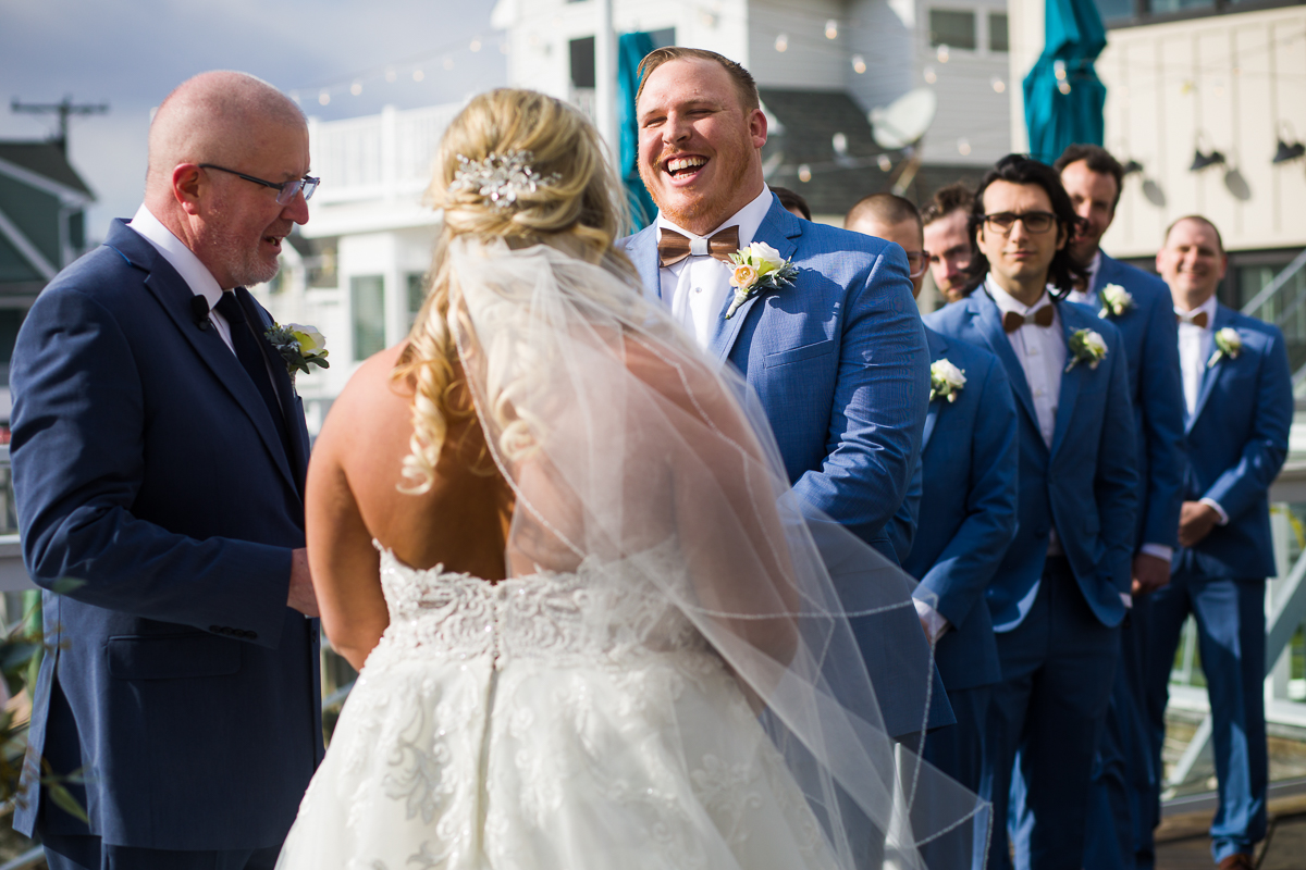 groom laughs during reeds stone harbor wedding ceremony
