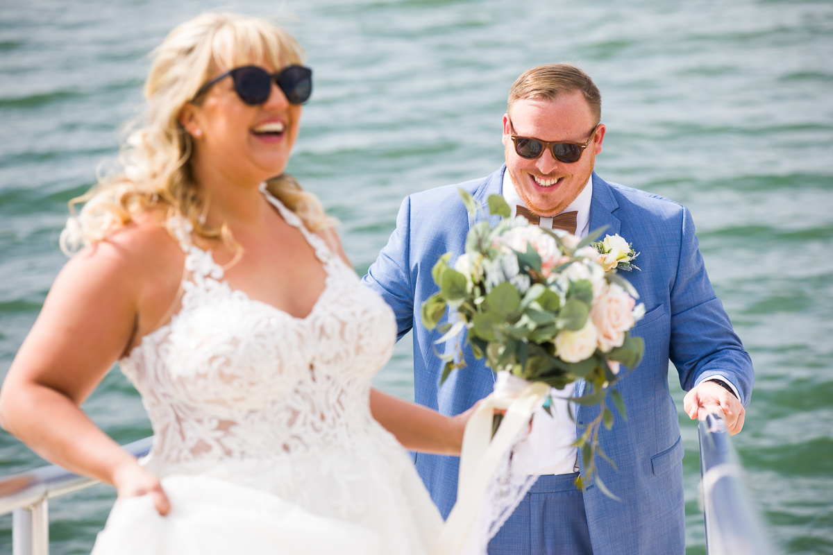 couple laughing wearing sunglassees and wedding attire