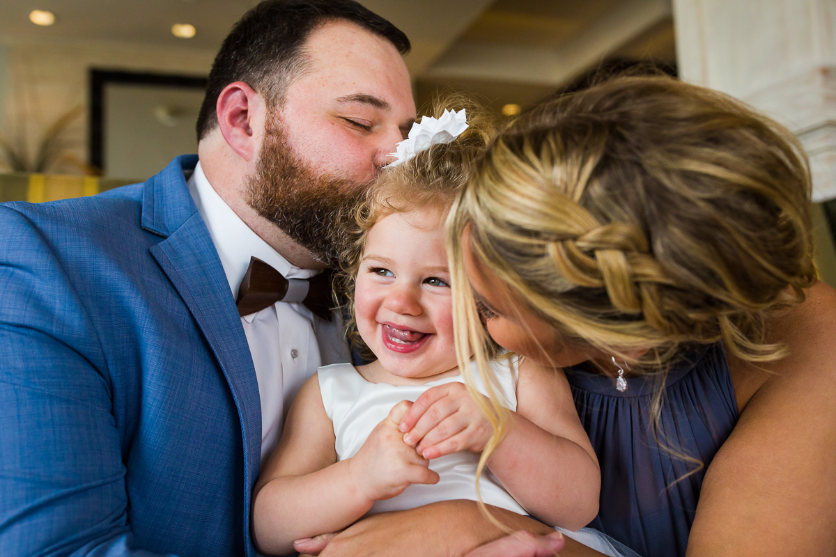 cute flower girl is kissed by her parents at the reeds in stone harbor nj