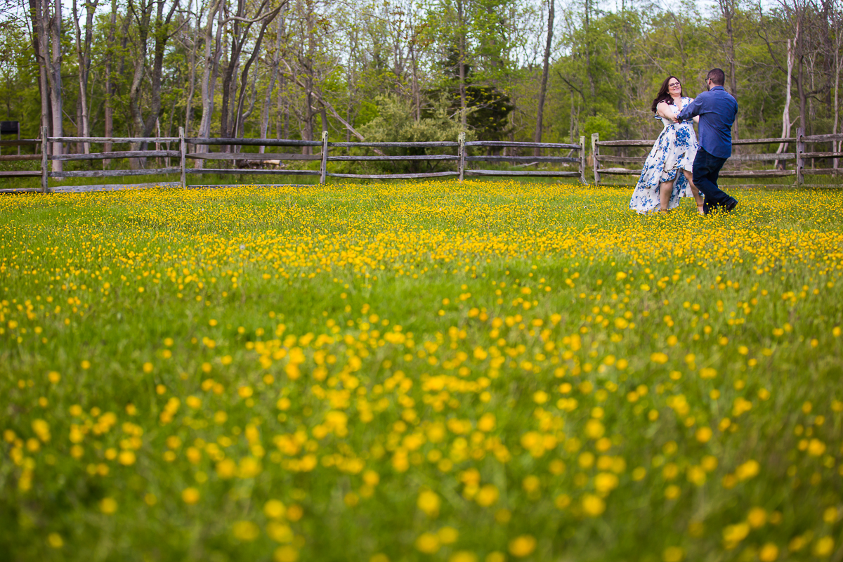 couple spins in a field of yellow buttercups during their Allaire Park Engagement