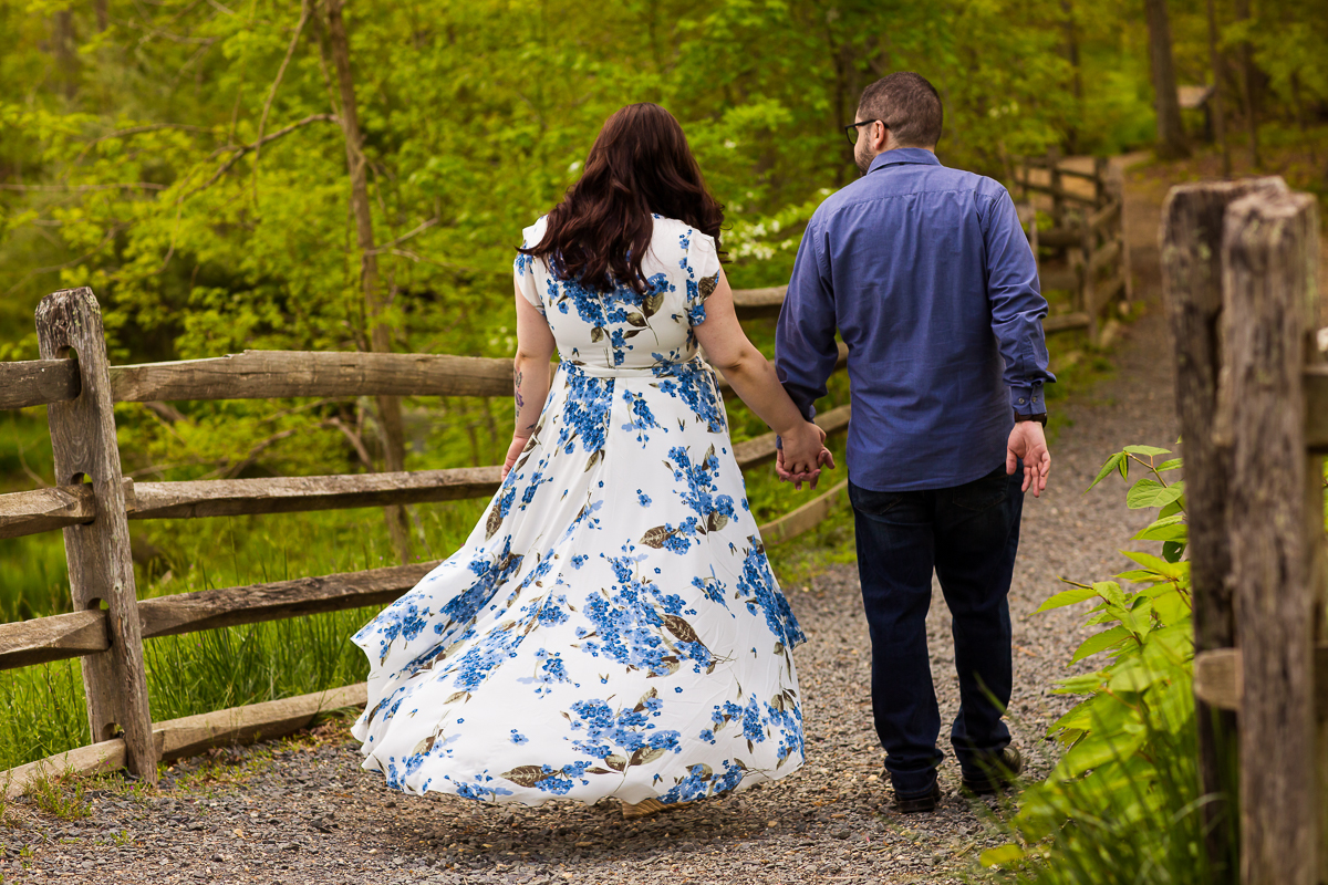 couple holds hands as the woman's dress catches the wind in her Allaire Park Engagement session