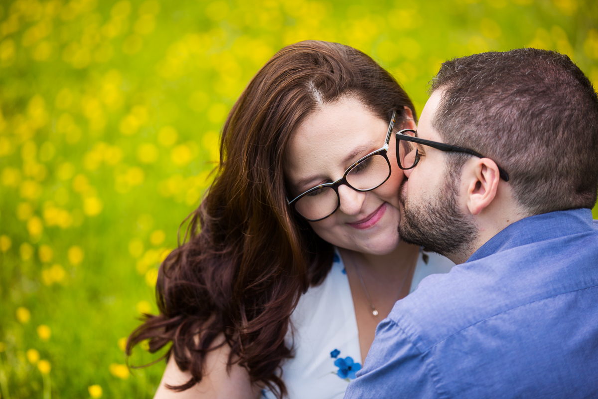 engaged couple wearing glasses, groom kisses bride's cheek