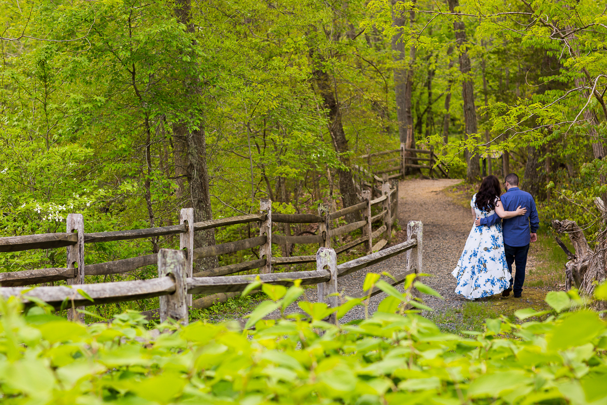 couple walks Spring green tree-lined path together in Allaire Park Engagement
