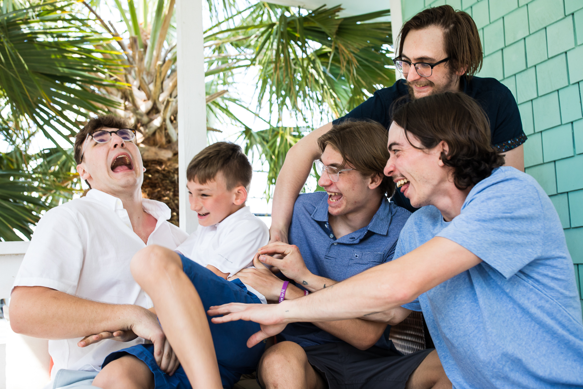 brothers tickle eachother on the porch of their family's beach house