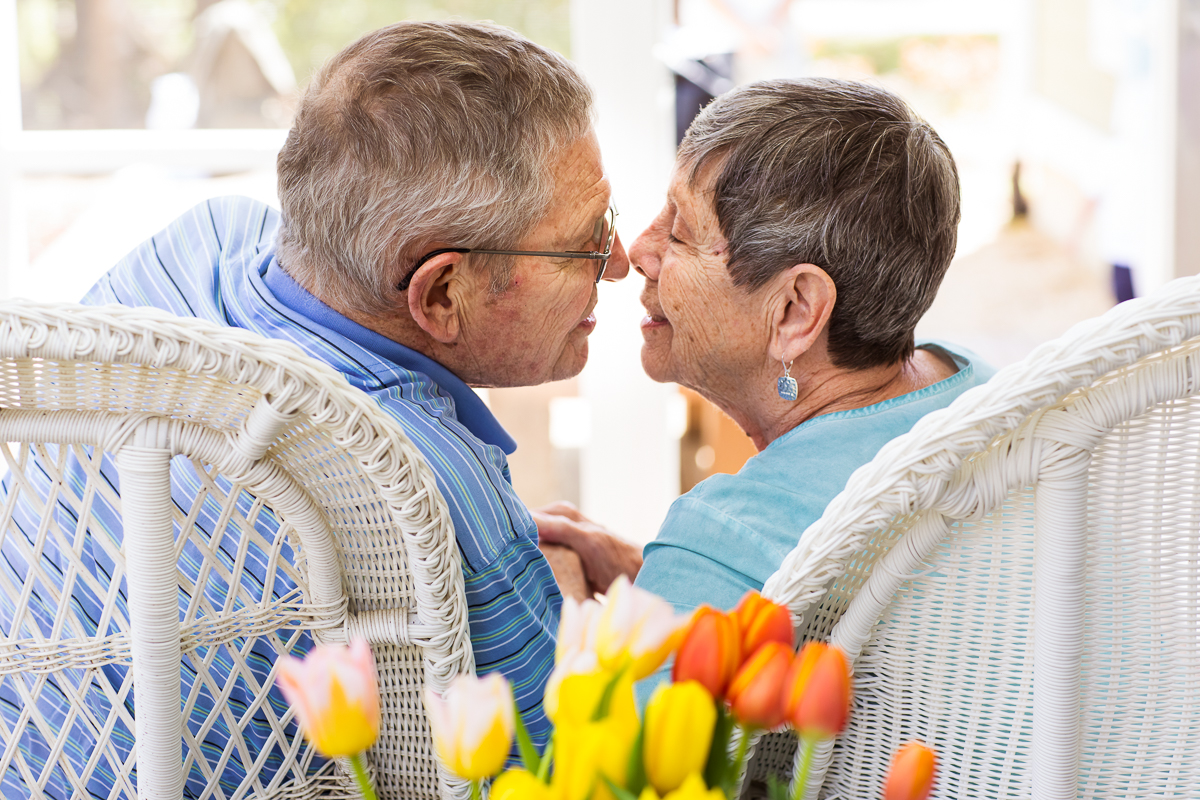 grandparents kissing in front of tulips everlasting love