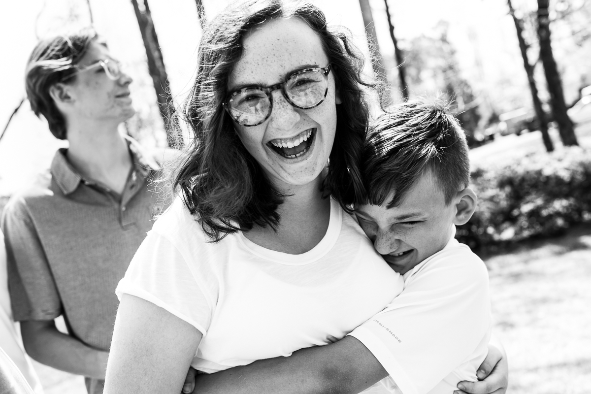 hershey pennsylvania family vacation photographer captures freckled sister laughing while her brother hugs her, she is wearing glasses in this black and white photograph