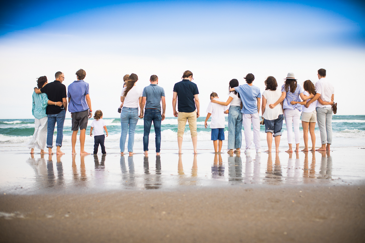 extended family gathers for award winning family vacation photographer as their backs are towards the camera and they face towards the ocean in wilmington NC