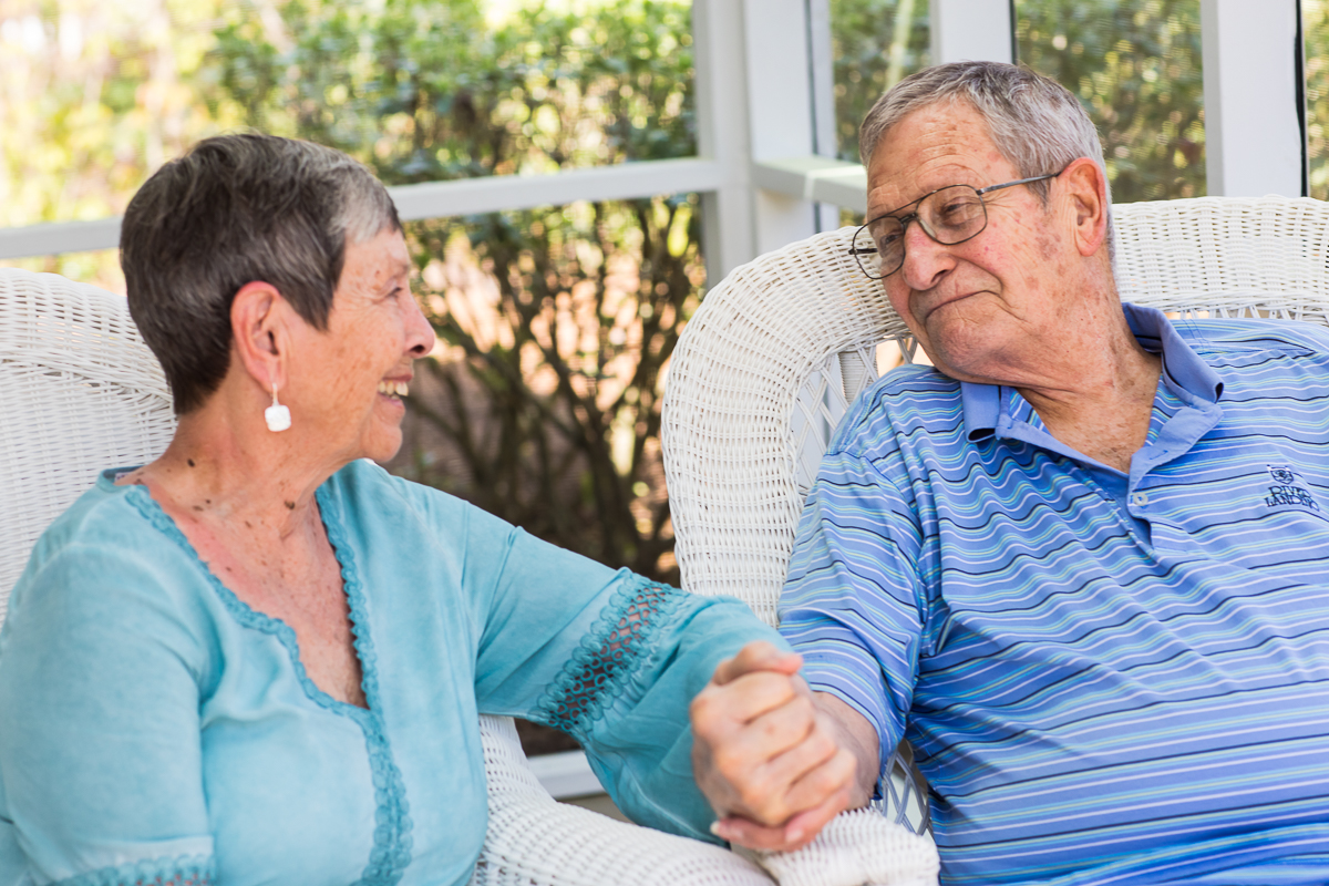 elderly couple in blue grandfather holds grandmothers hand lovingly marriage