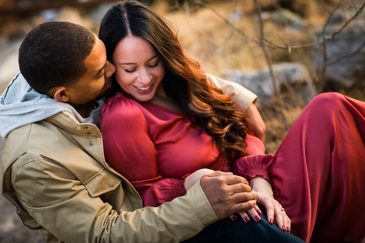 Engaged couple wearing khaki and a red dress hugging in reading pennsylvania