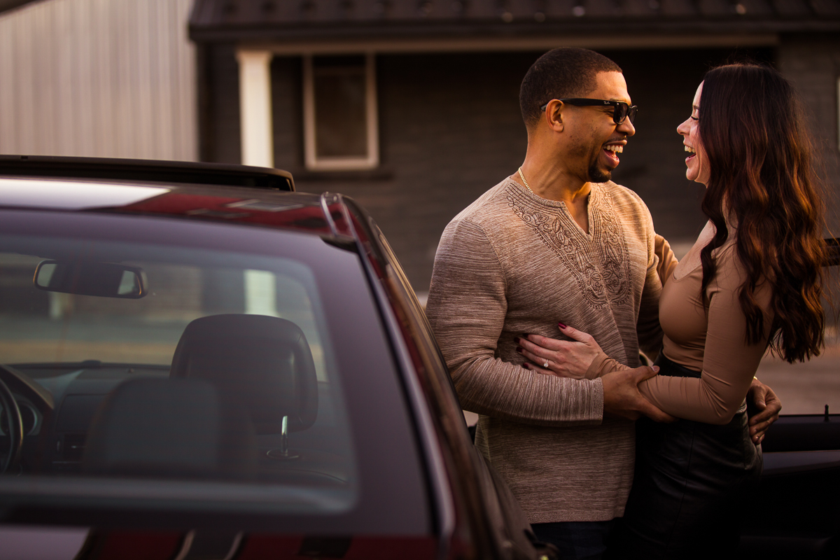 laughing newly engaged couple beside their car in Reading PA