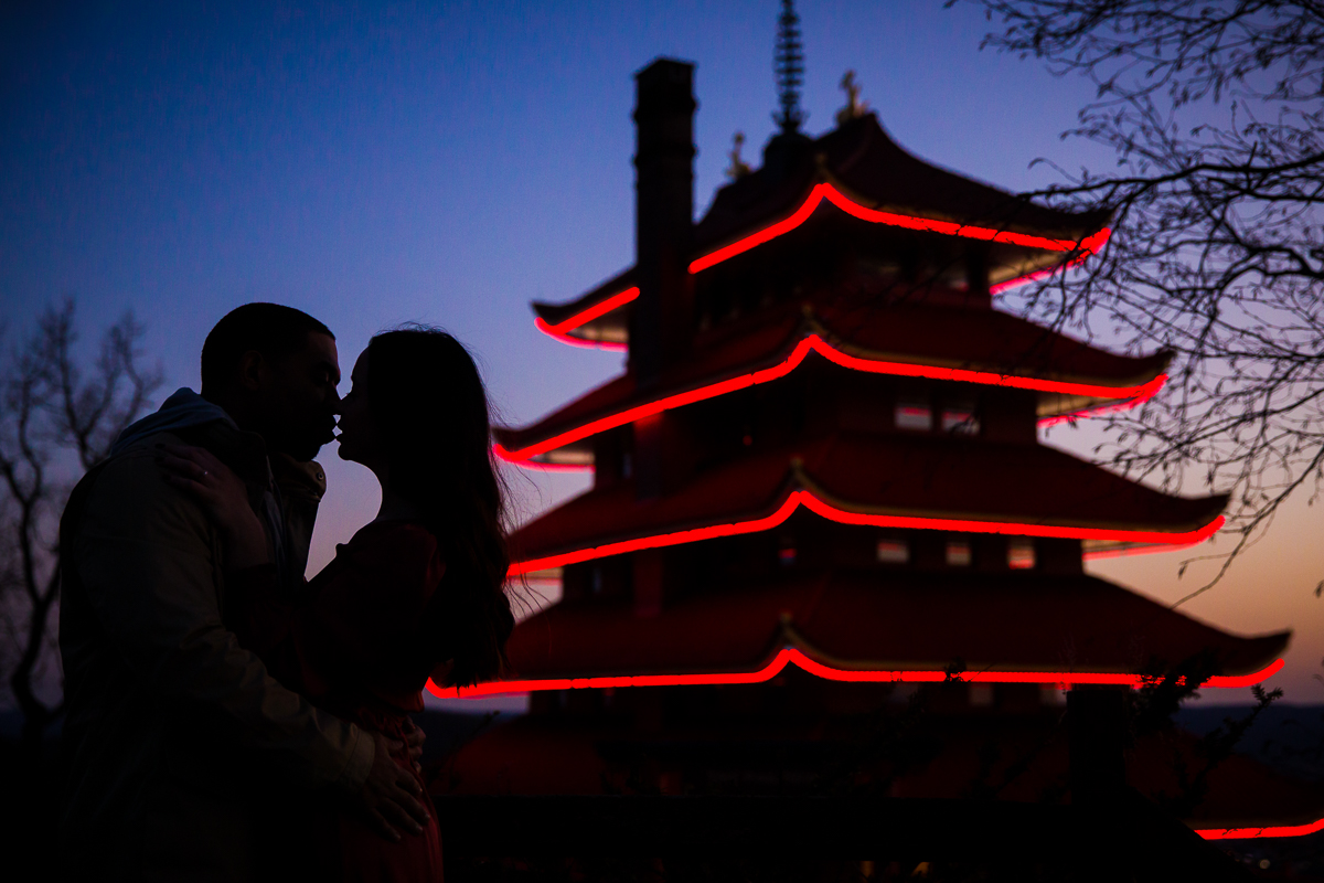 Engaged couple creatively silhoetted against unique Pagoda in reading pennsylvania during their engagement photography session