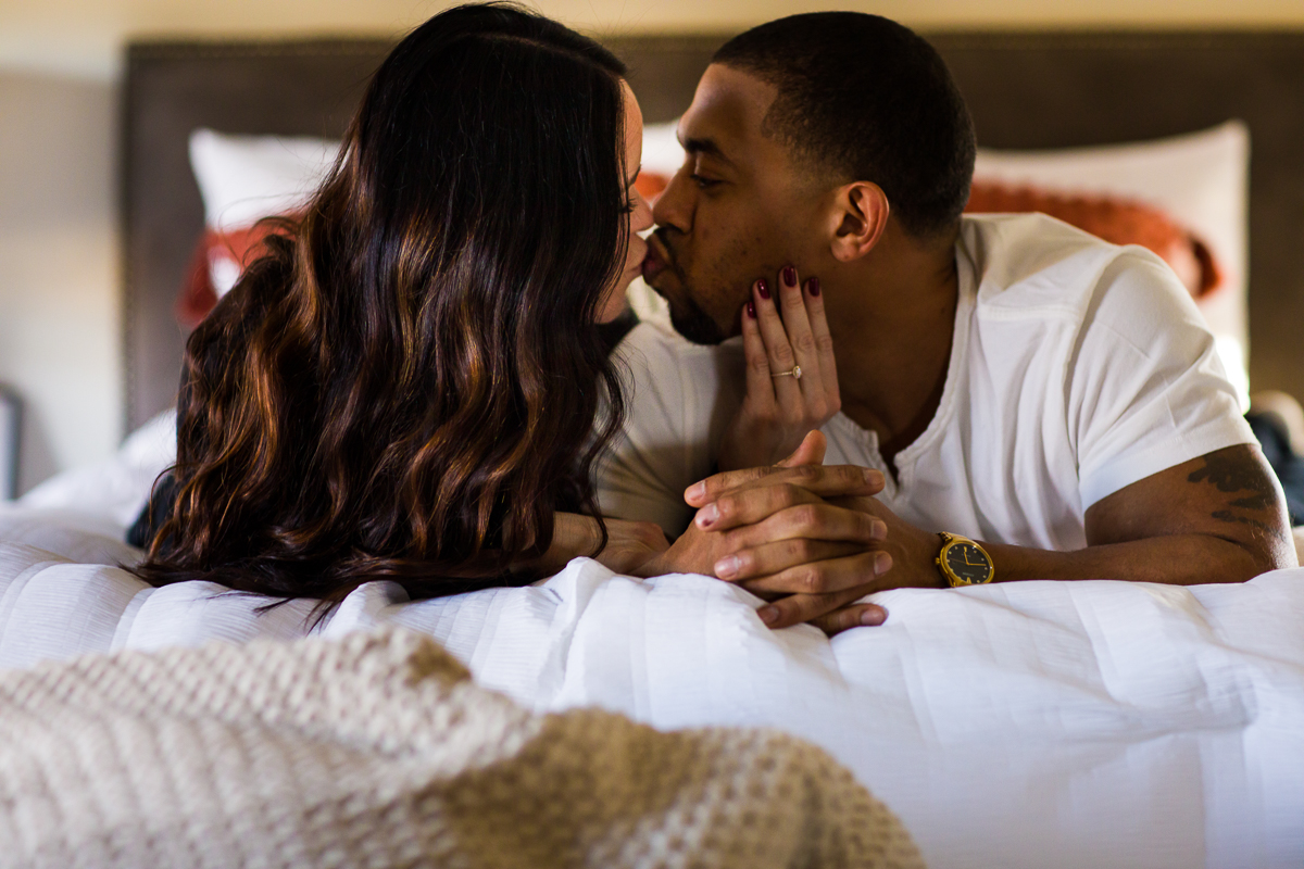 newly engaged couple laying on bed kissing for sweet natural candid photography session