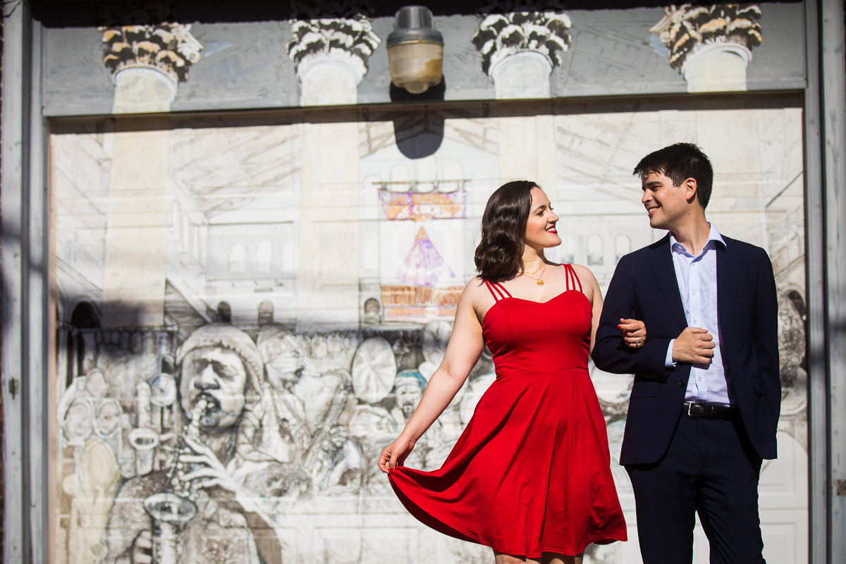 engaged couple walk in front of blagden alley mural in a red dress and suit DC Blagden Alley & NGA Engagement