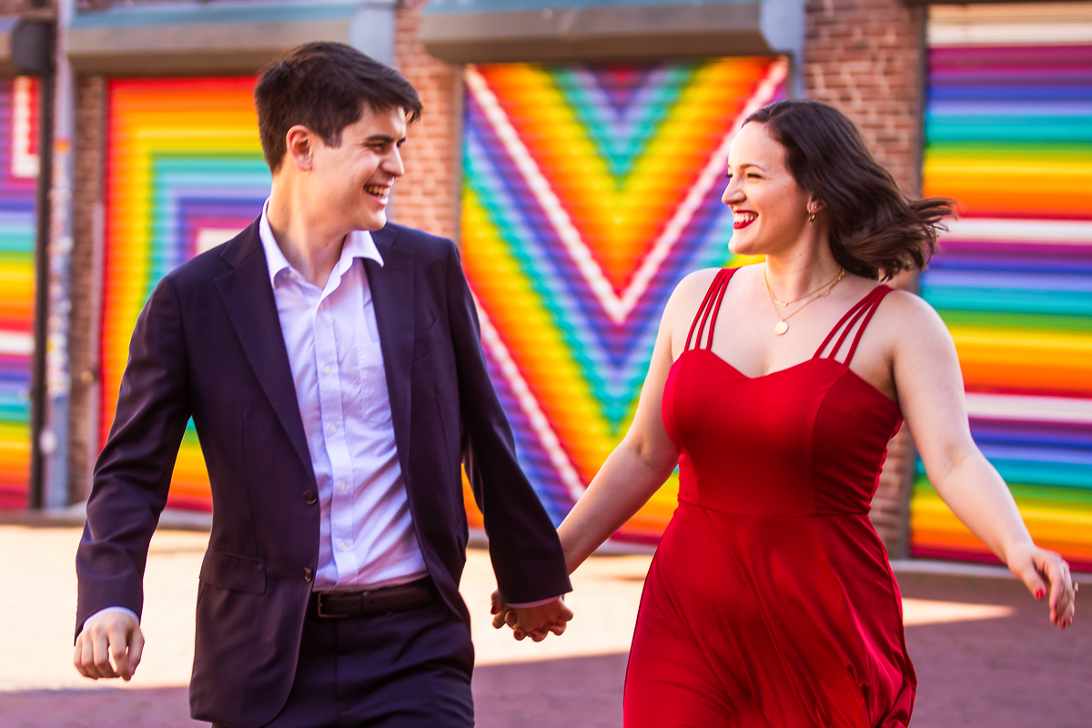 DC Blagden Alley & NGA Engagement vibrant blagden alley rainbow mural DC couple laughing and walking during Engagement Photography at National Gallery of Art