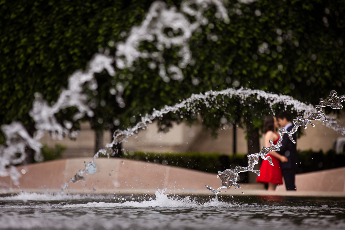 artistic creative photo of water droplets in fountain with couple in background during their national gallery of art sculpture garden DC Blagden Alley & NGA Engagement