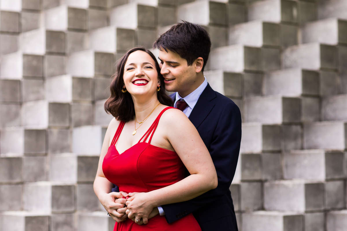 national gallery of art sculpture garden engaged couple in front of gray block wall mural red dress and suit DC Blagden Alley & NGA Engagement
