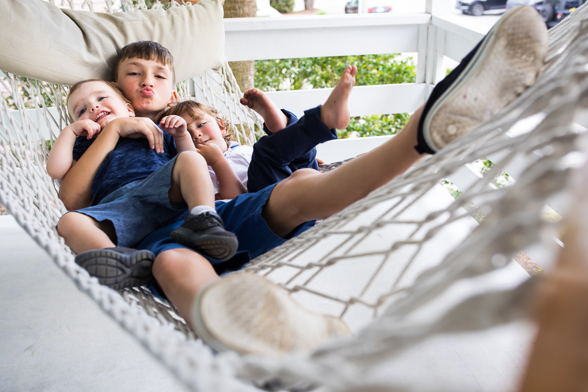 young family members gather together on vacation in their hammock