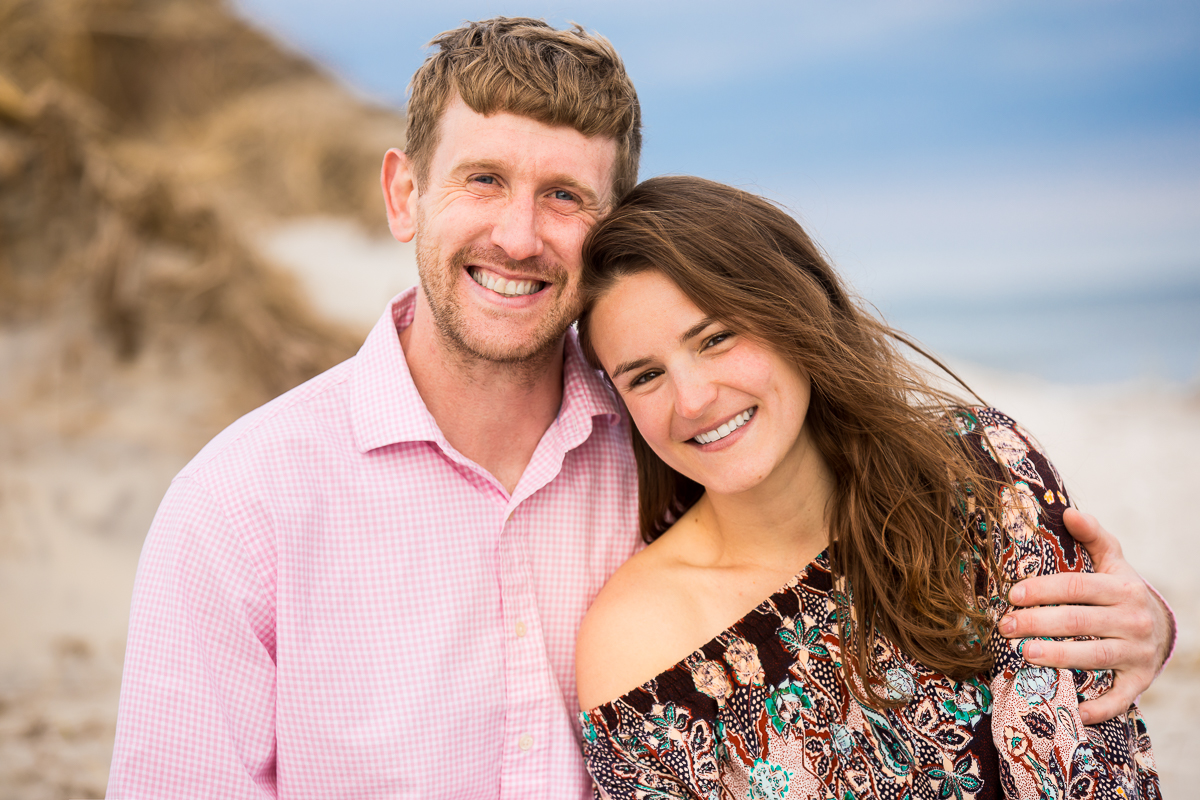 wildwood crest engagement photographer creative best captures couple smiling in beach portrait wearing pink and brown in front of the ocean