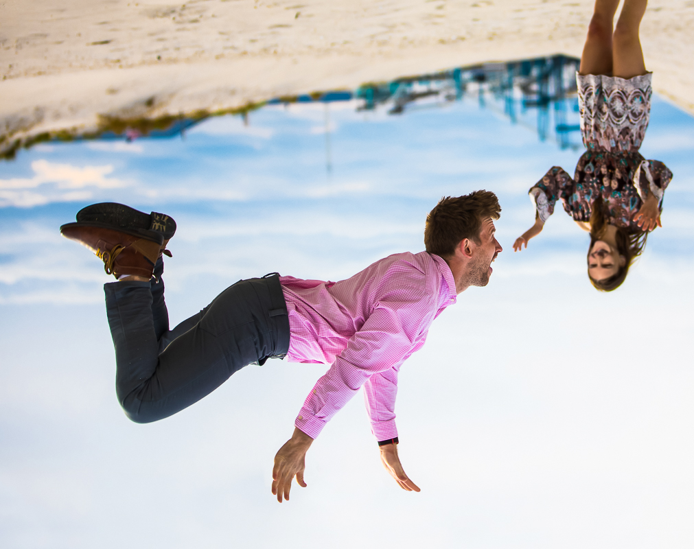 fun athletic engagement photo of man doing backflip on the beach in wildwood nj with the boardwalk in the background