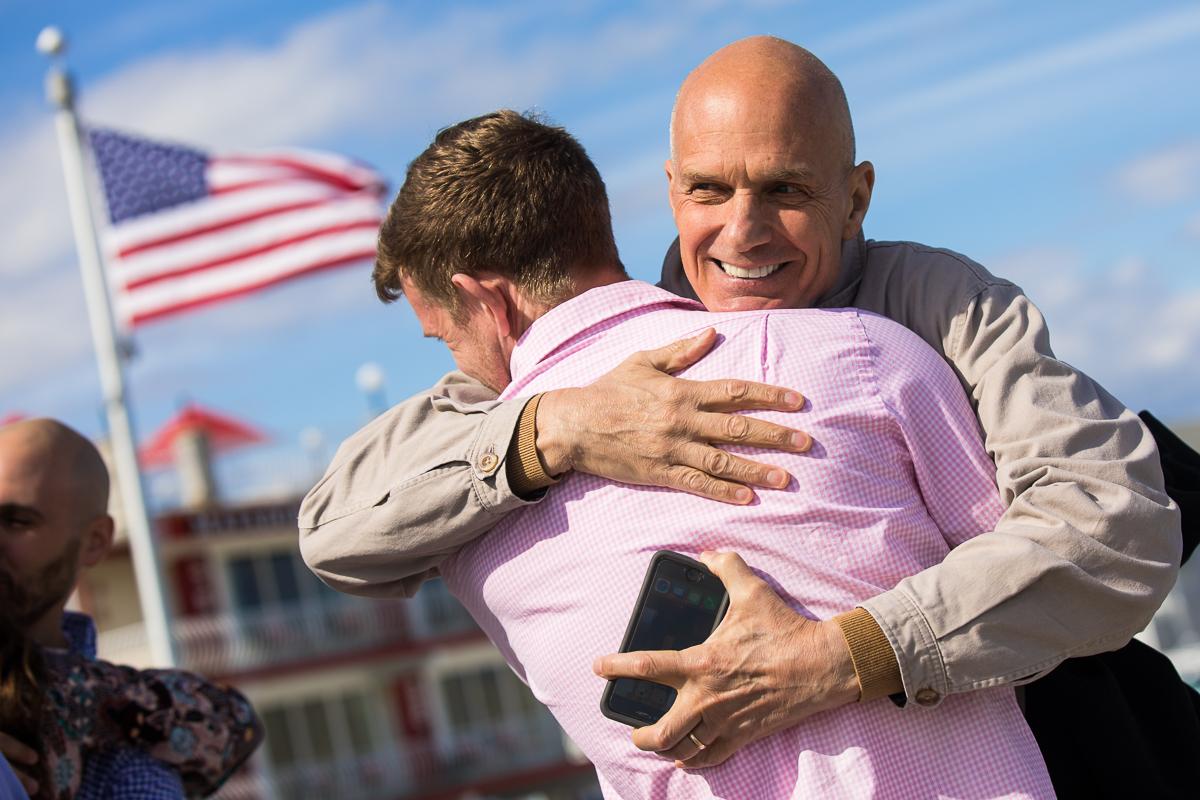 father-congratulating-son-beach-proposal
