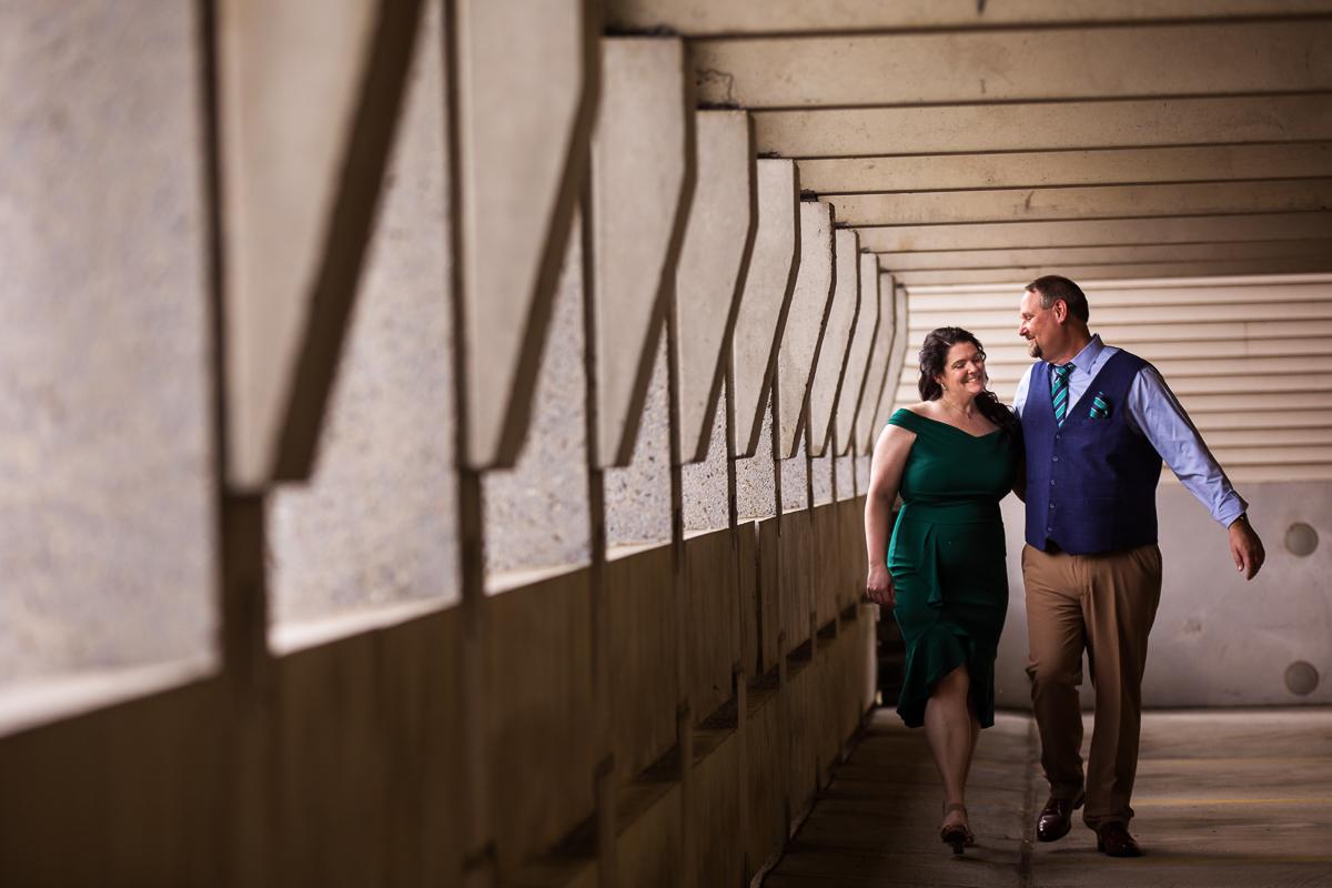 couple walking through parking garage in formal attire