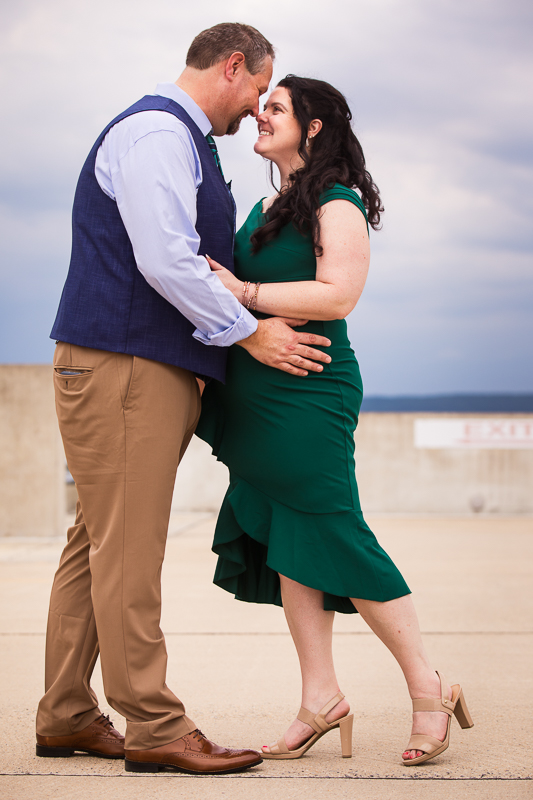 couple wearing formal attire smiling at each other during engagement session