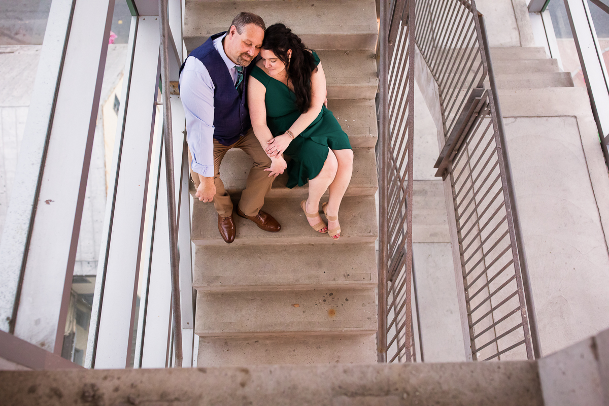 engagement session couple sitting on stairs in parking garage