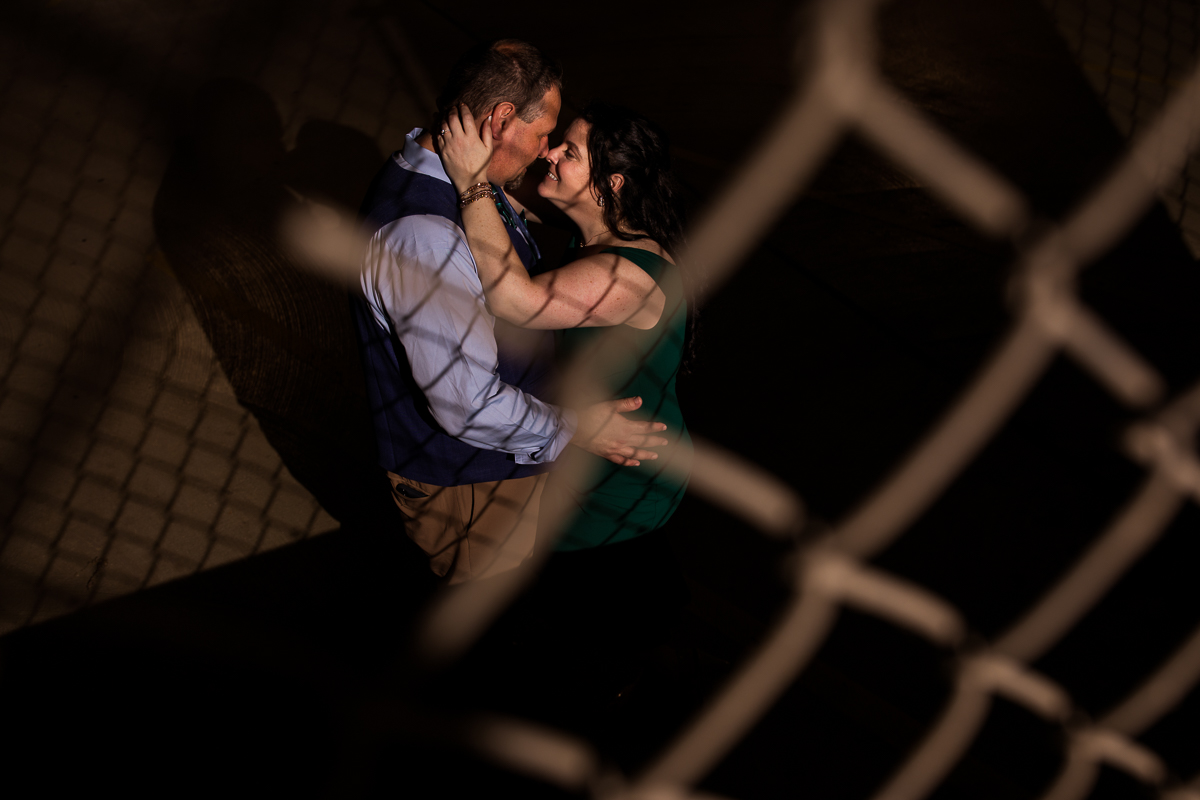Downtown Harrisburg engagement session photo creative night through chain link fence