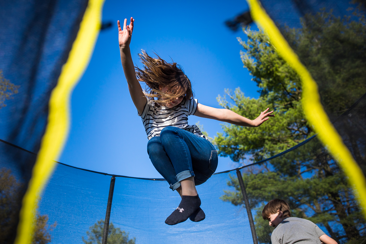 creative candid photo of girl jumping on trampoline wearing under armour socks and striped shirt