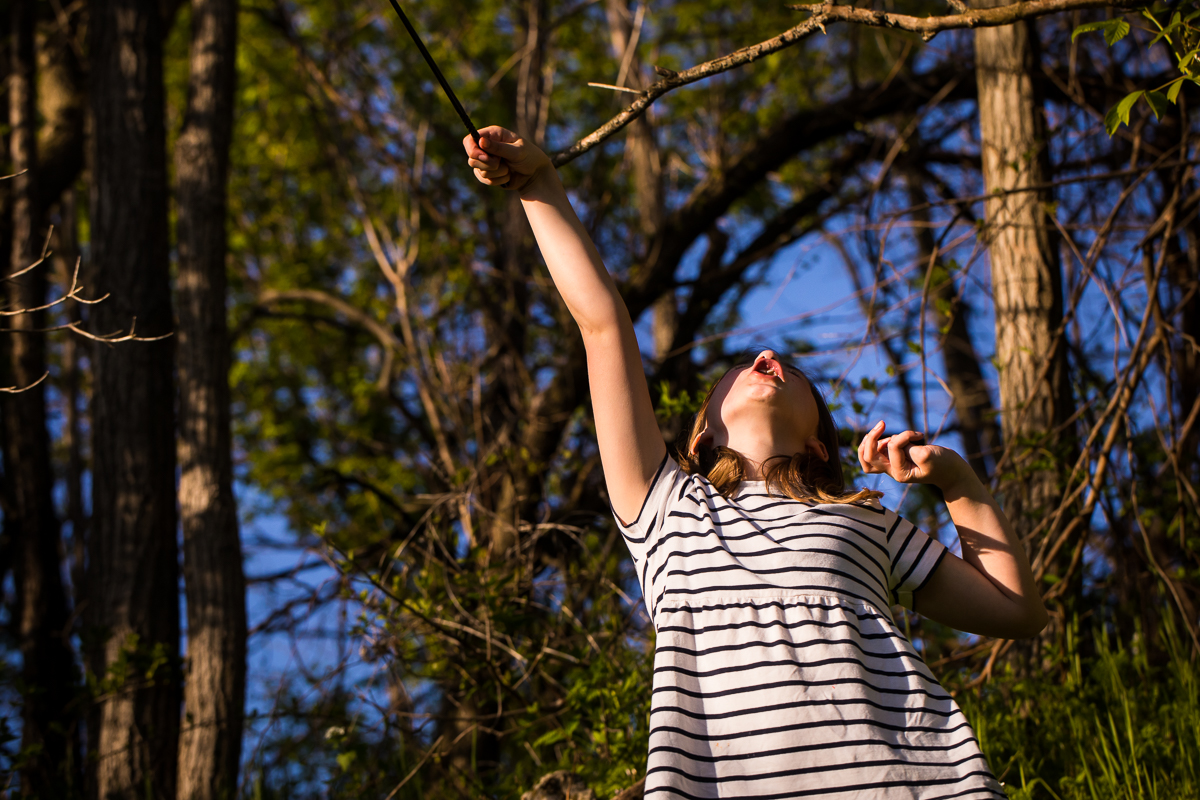 girl with wand pretending to cast a spell like Harry Potter fun outdoors