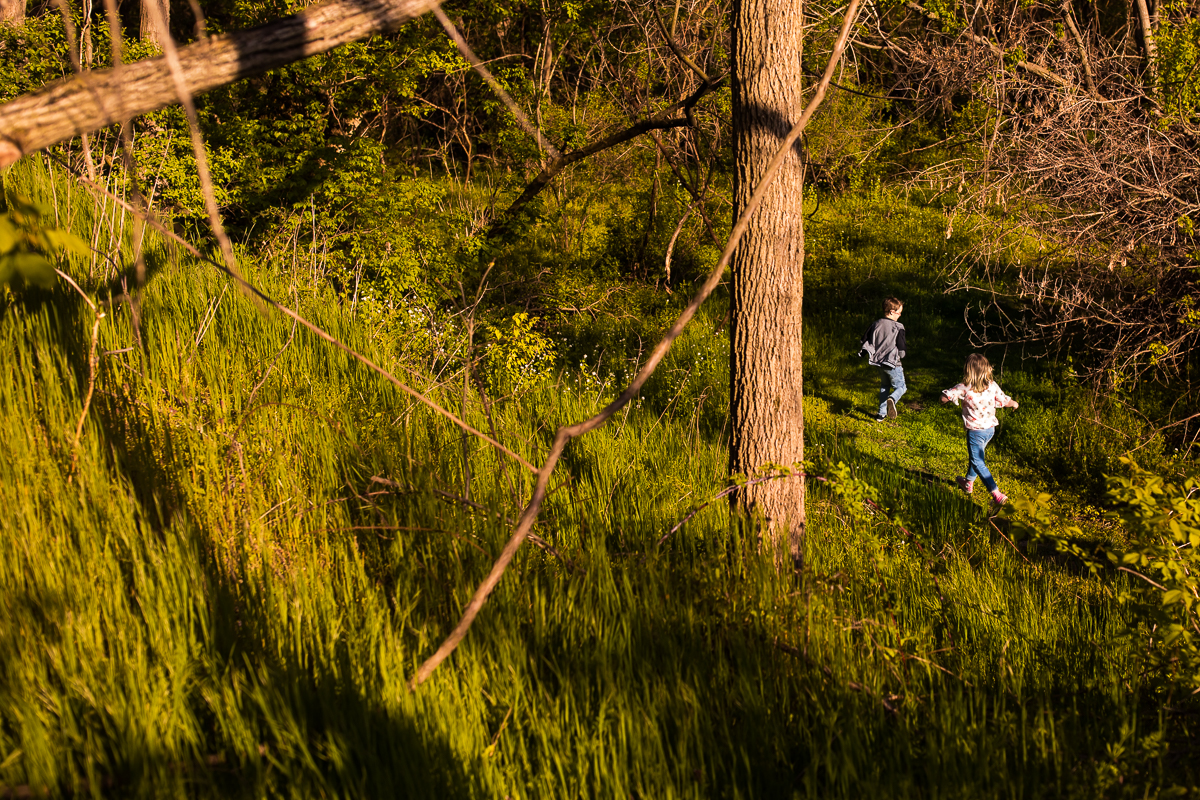 creative wide angle shot of brother and sister running through woods outdoors in their backyard