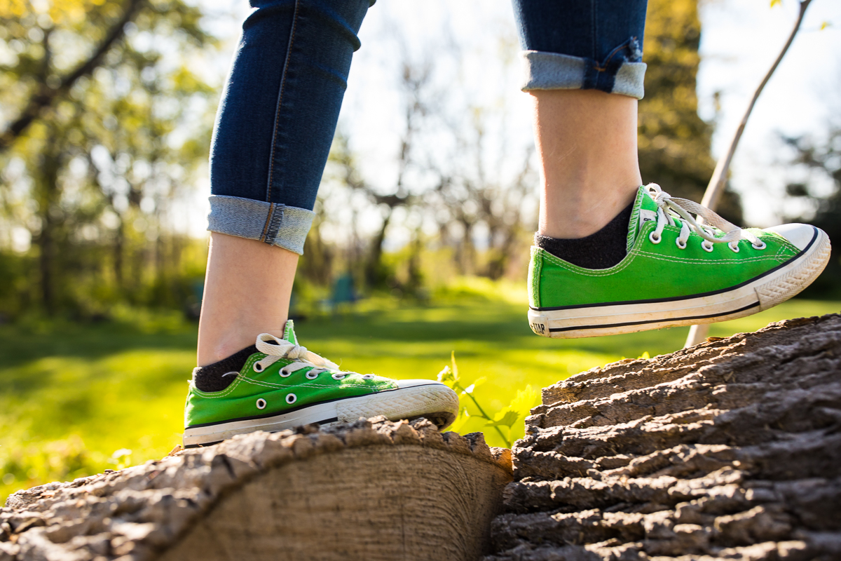 girl walking on log wearing vibrant green converse sneakers during pennsylvania outdoor family session creative angle
