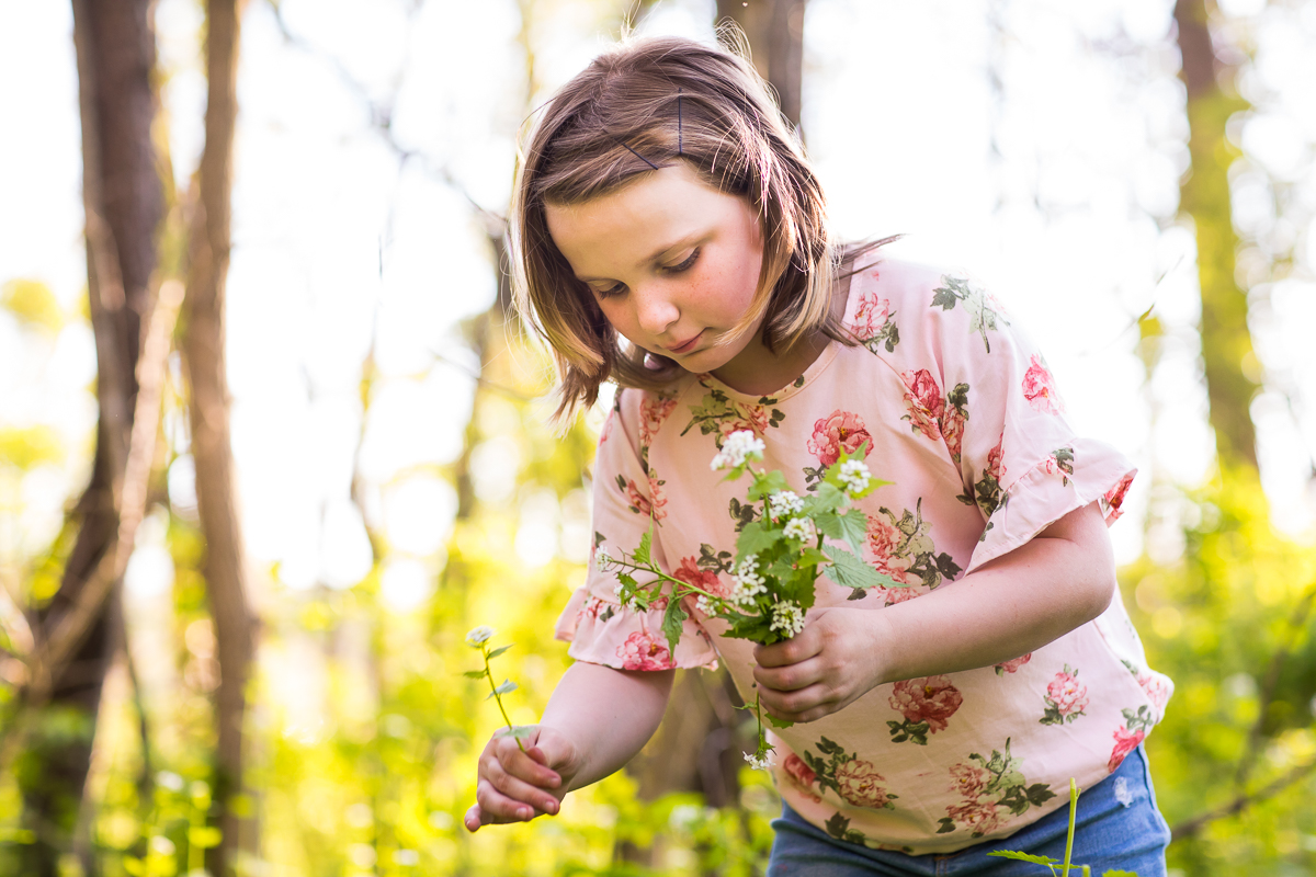 child in pink floral shirt collecting flowers to make crown during family session