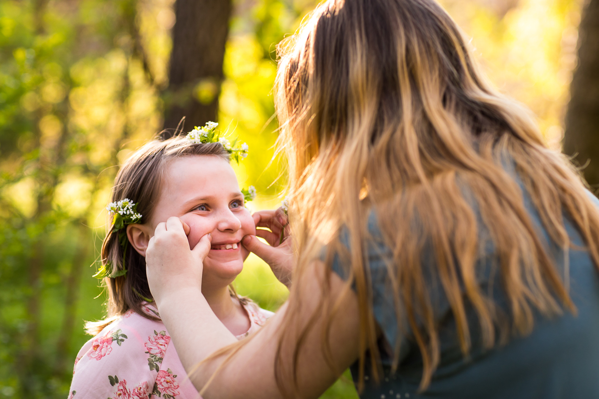 mom pinching daughters cheeks as she smiles with hand made flower crown outdoors