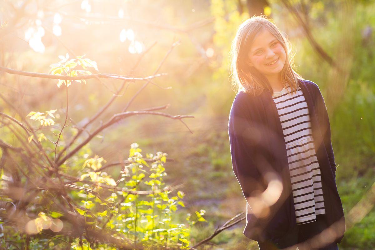 solar flare during portraits with girl in woods wearing striped shirt