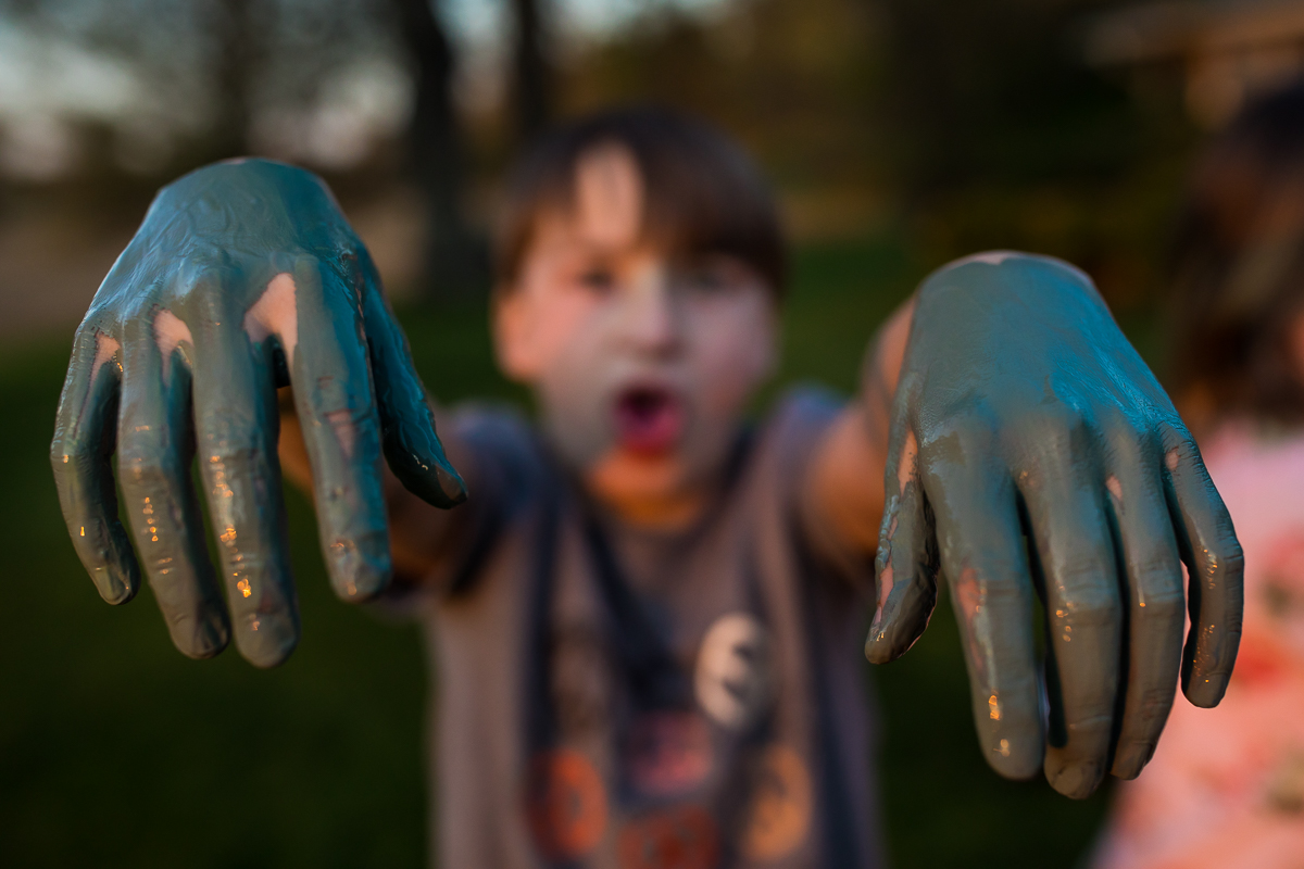 boys hand covered in paint while making silly face at camera
