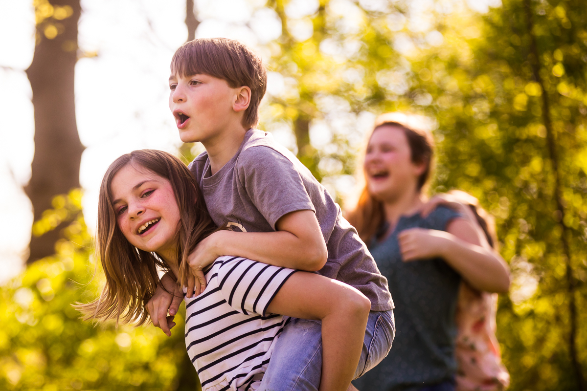 best pennsylvania family photography photographer girl carrying brother on back while siblings laugh in the background