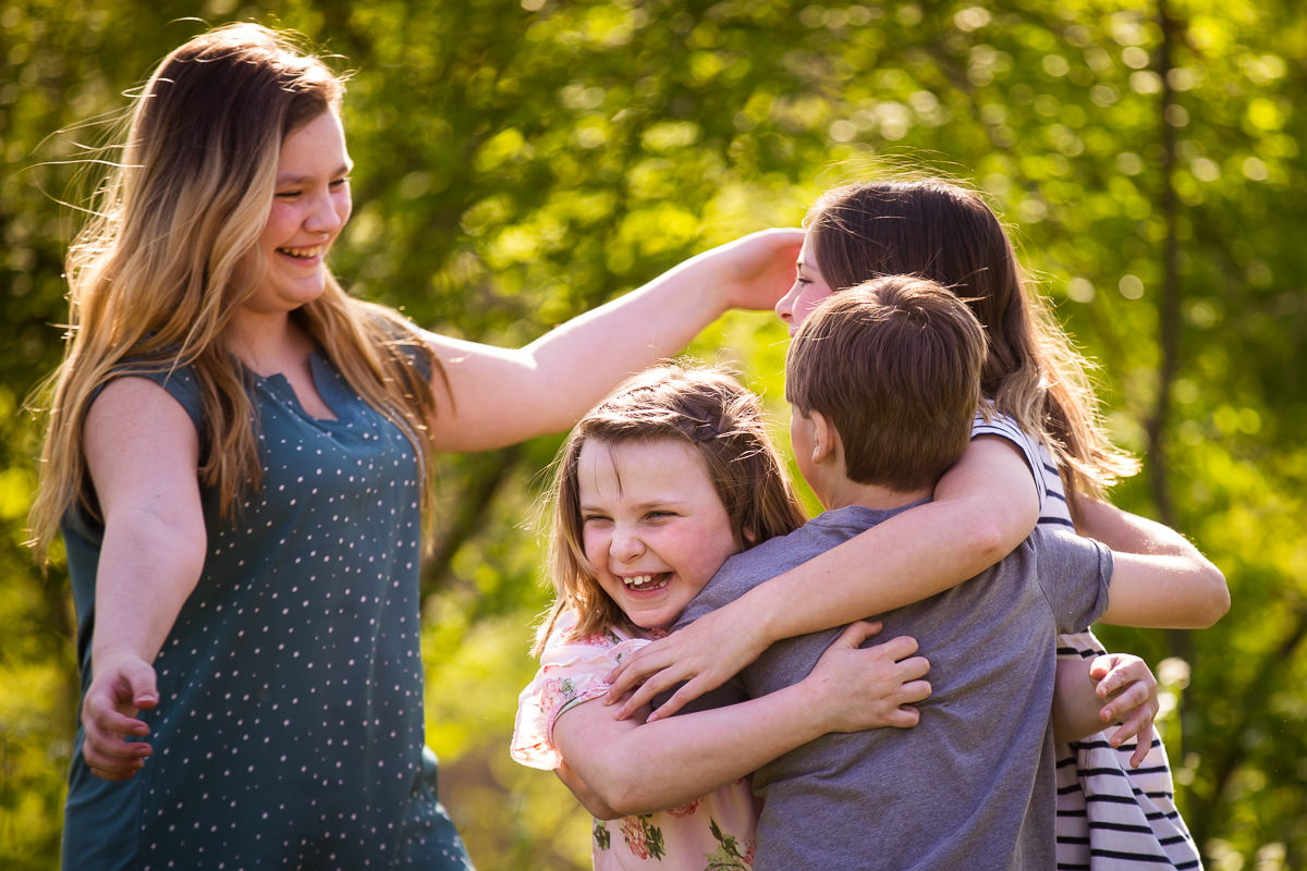 brothers and sisters hugging outside during pennsylvania family session