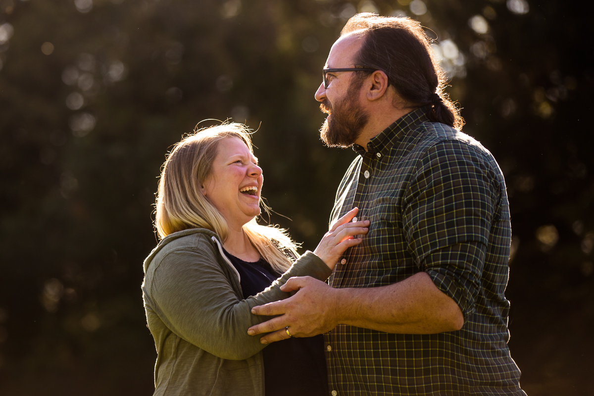 couple laughing and smiling during candid portrait outdoors