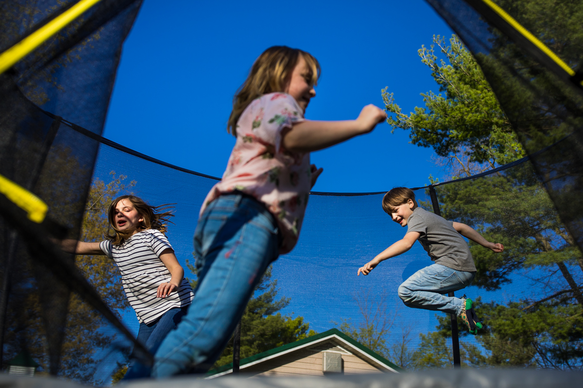 three kids jumping on trampoline in back yard with house in distance fun angle
