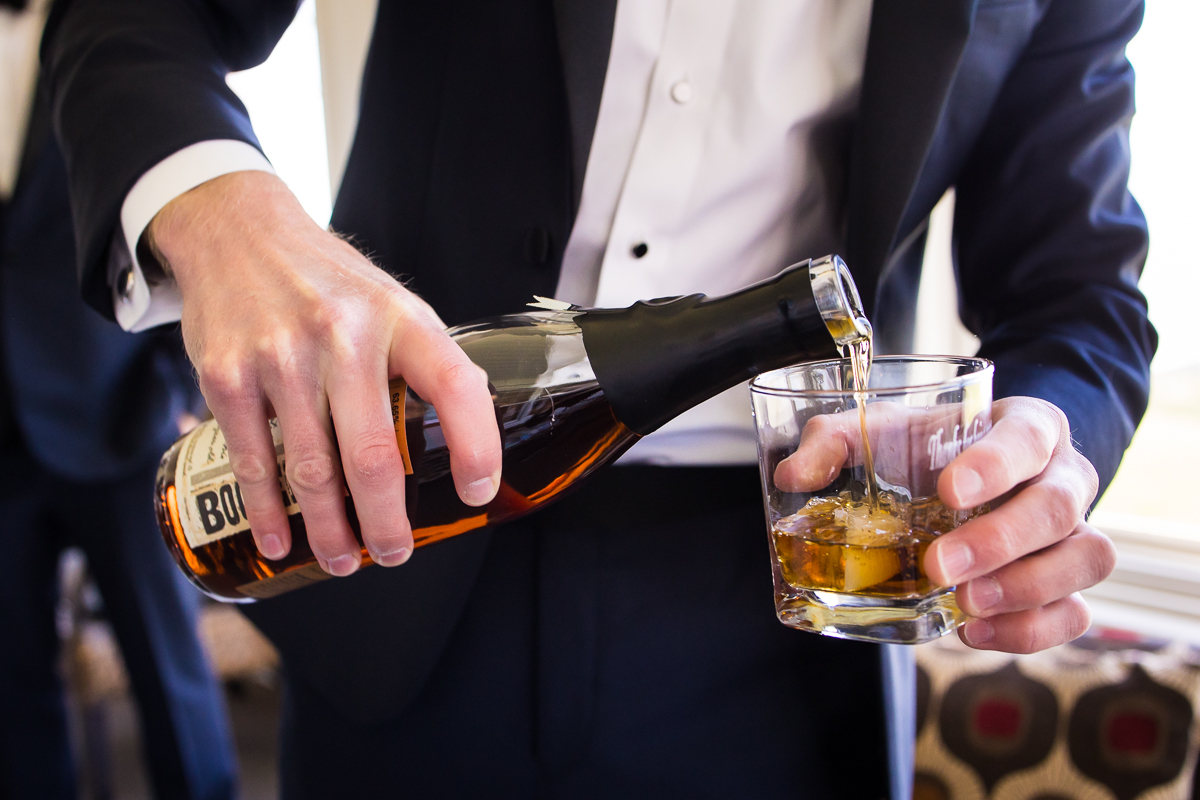 artistic photo of groom in Stevensville Maryland pouring glass of bourbon in suit