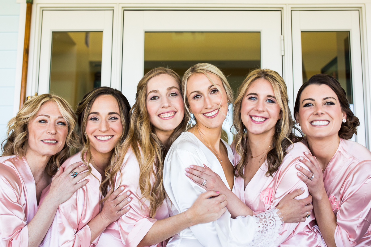 bridesmaids in pink robes outside smiling with best Stevensville Maryland wedding photographer