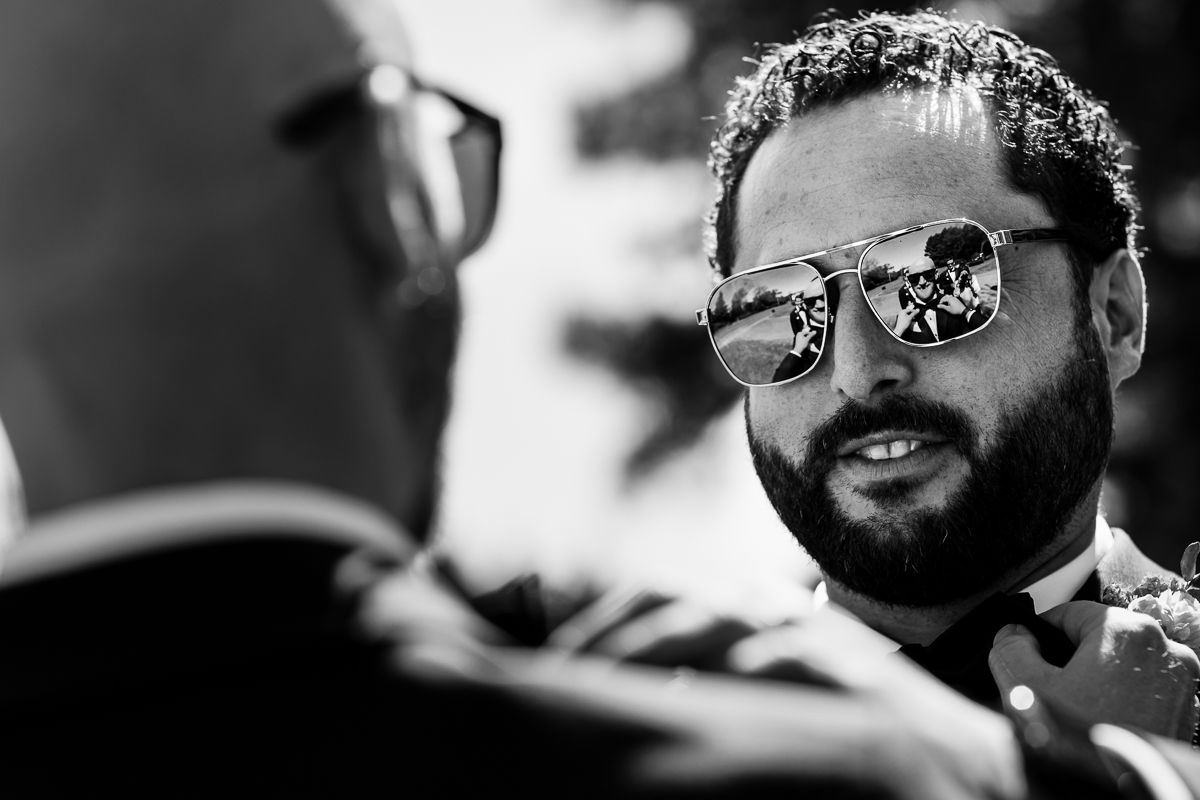fun candid of groom reflecting in groomsmen sunglasses in black and white