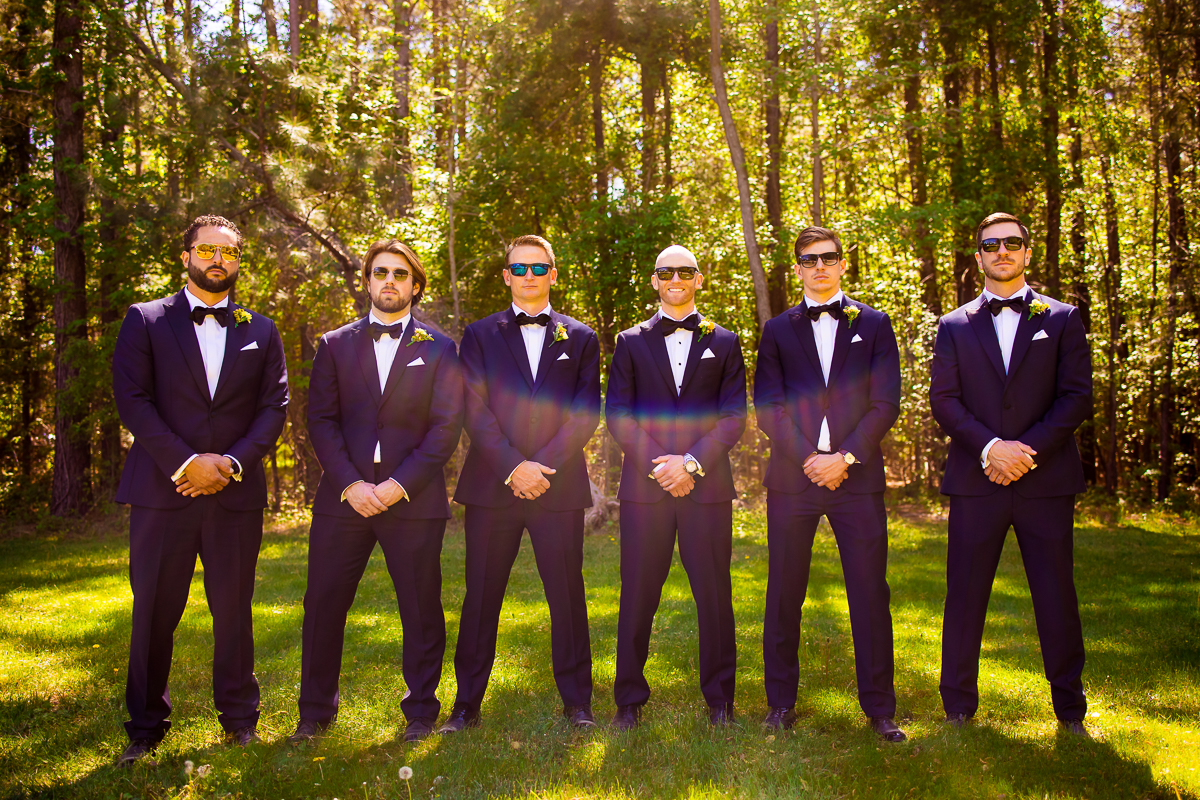 groomsmen in navy tuxes with sunglasses and solar flare at camp wright creative stevensville maryland wedding photographer