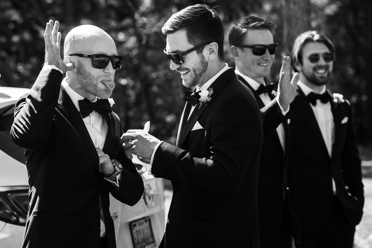groom making silly faces wearing suit with bowtie in black and white