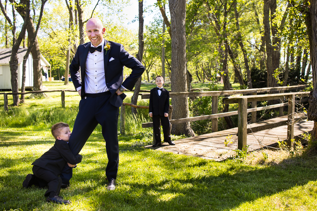 ring bearer holding on to grooms leg before wedding ceremony with best Stevensville Maryland wedding photographer