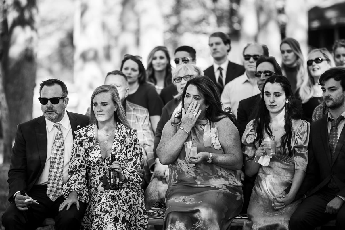 emotional guests reaction in black and white to couple exchanging vows