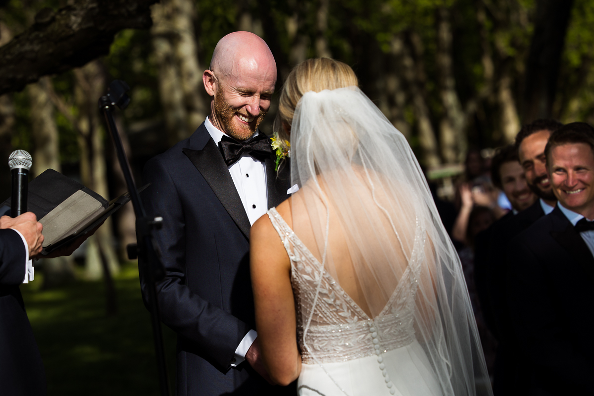 groom grinning from hearing bride read vows during wedding ceremony