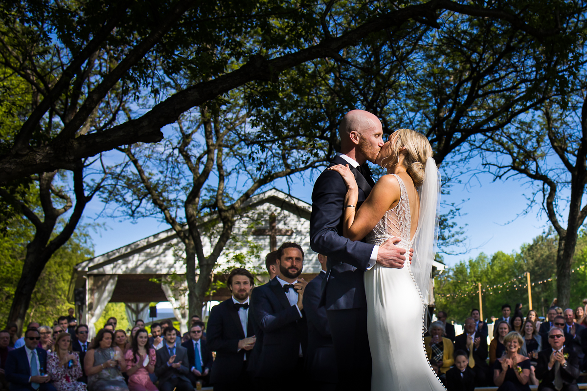 camp wright in stevensville maryland wedding best venues bride and groom first kiss with guests clapping