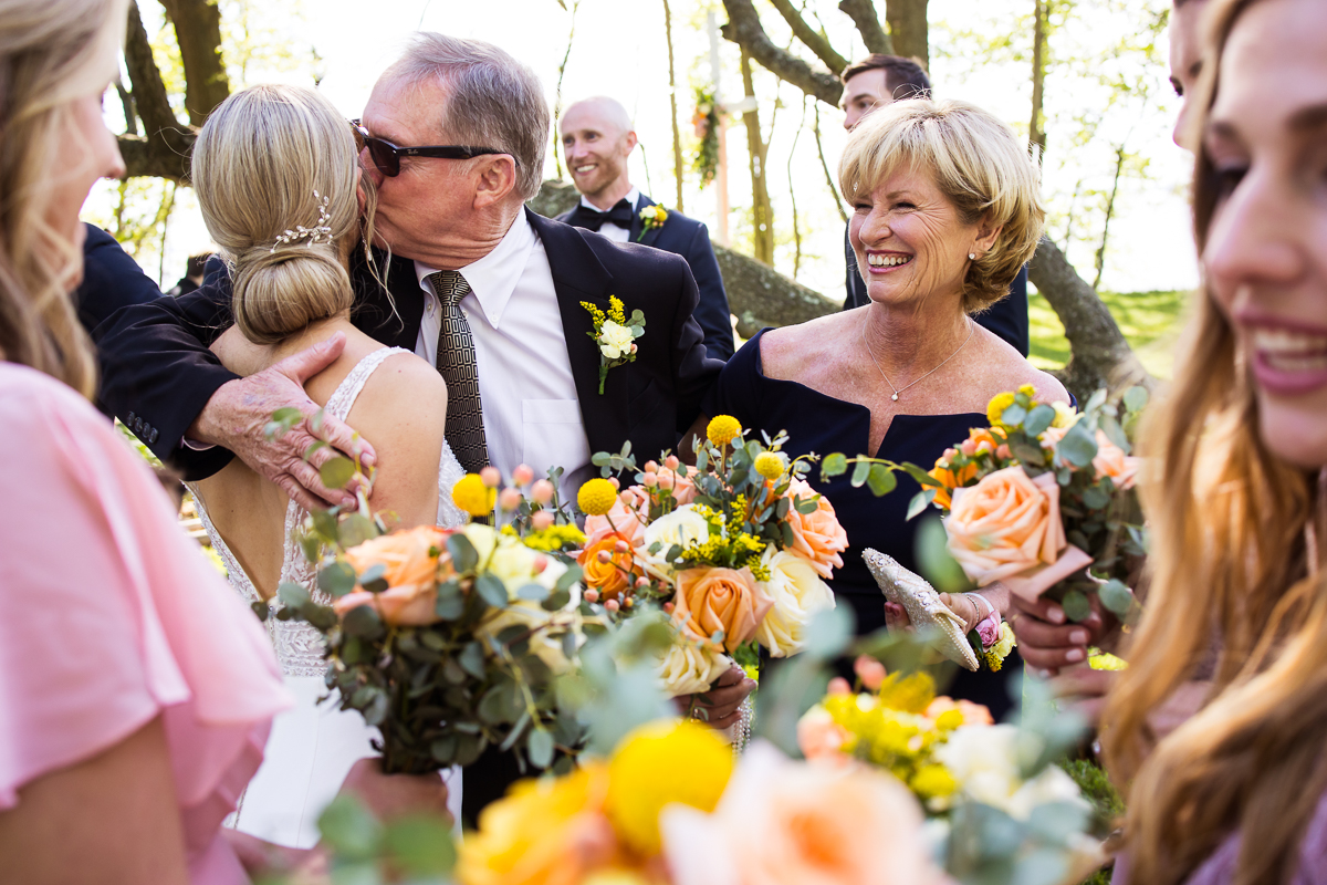 pink and orange bridal bouquet with father of the bride kissing on cheek